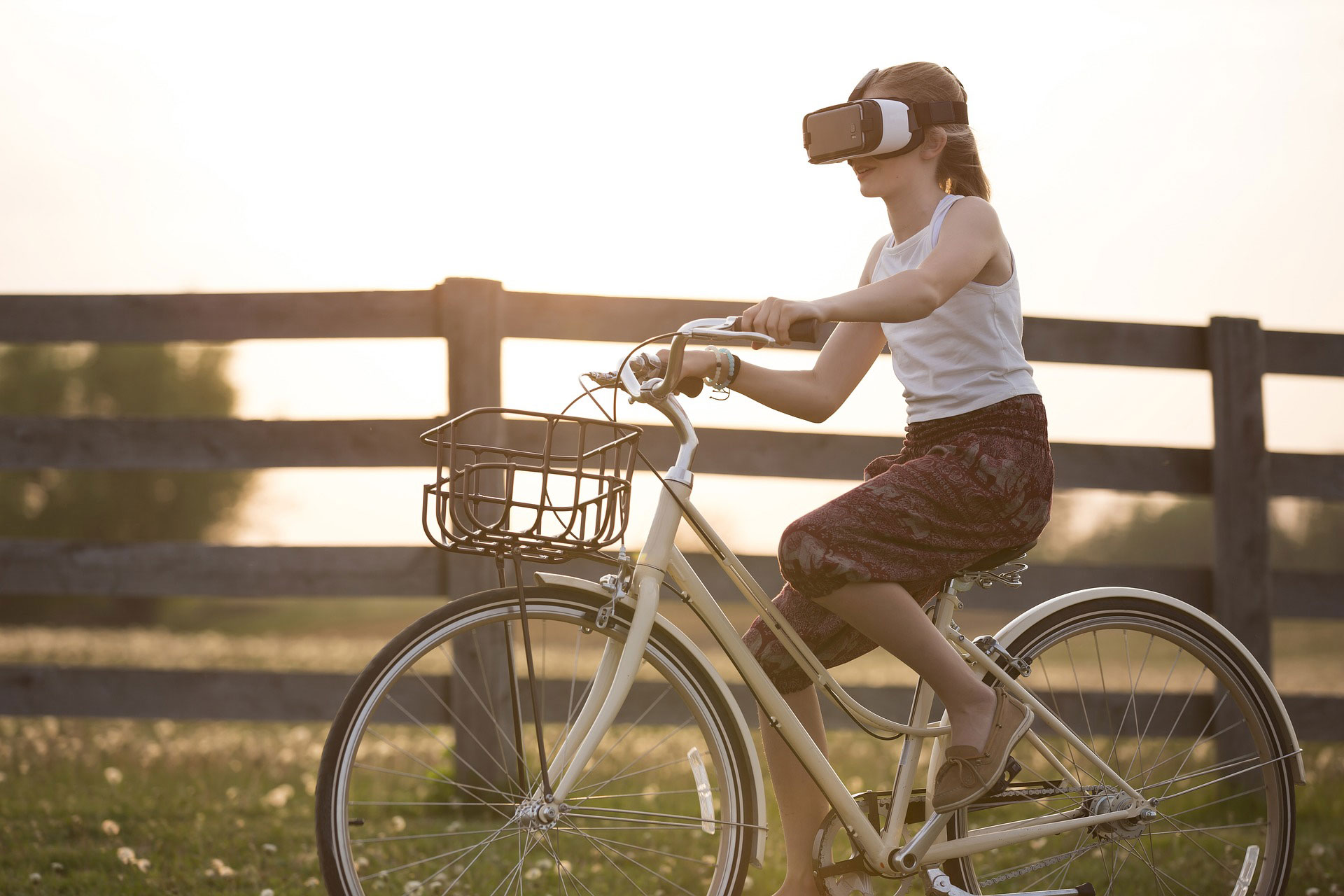A girl wearing VR glasses while on a bicycle